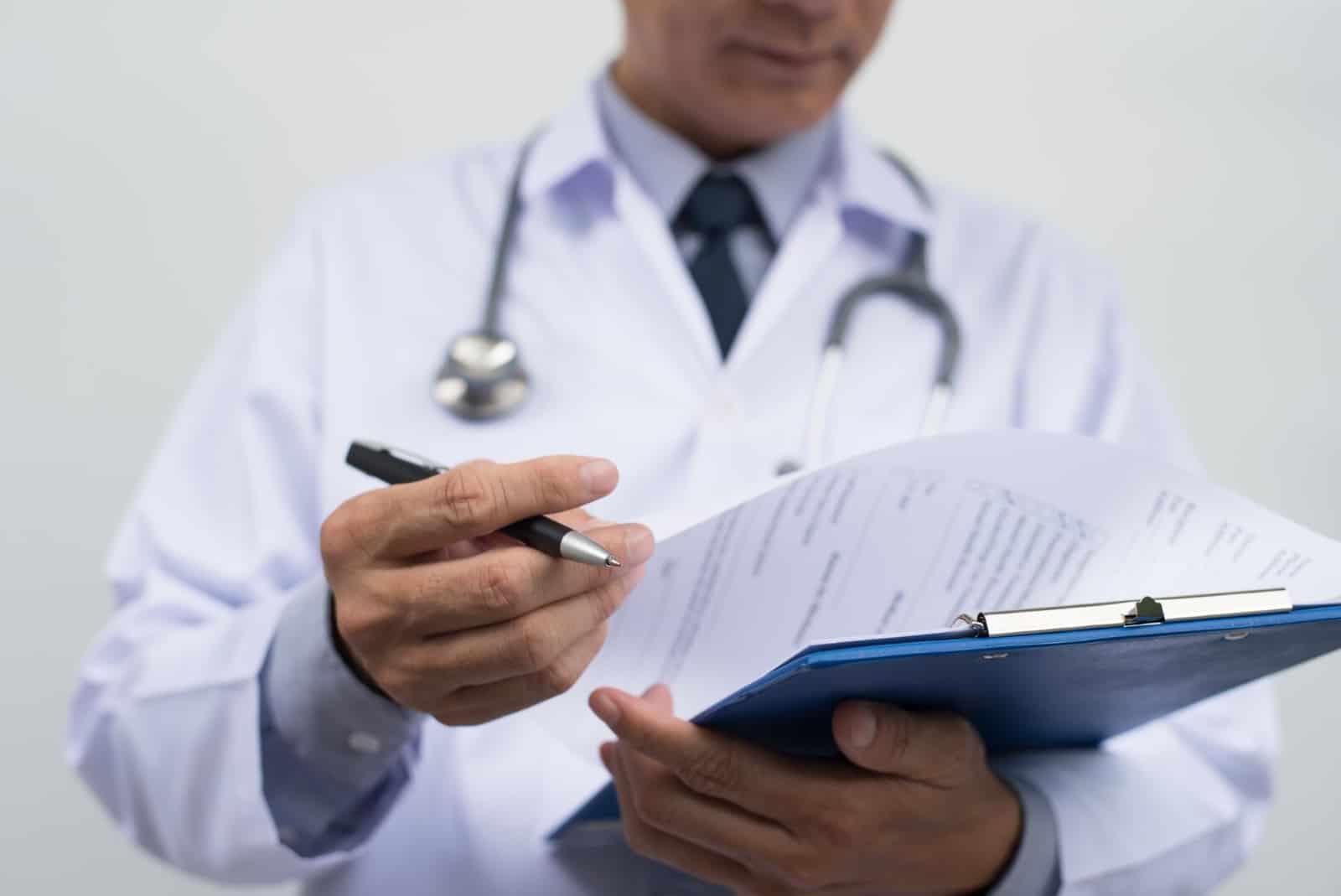 best functional medicine doctor: Doctor reading his patient notes