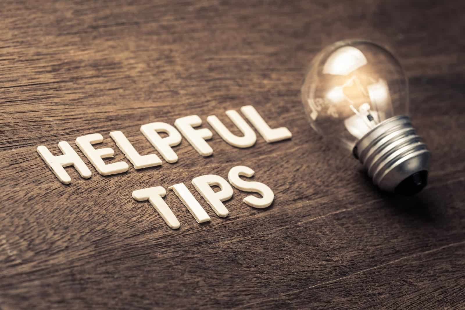 Helpful tips spelled out on a wooden surface with a lightbulb beside it