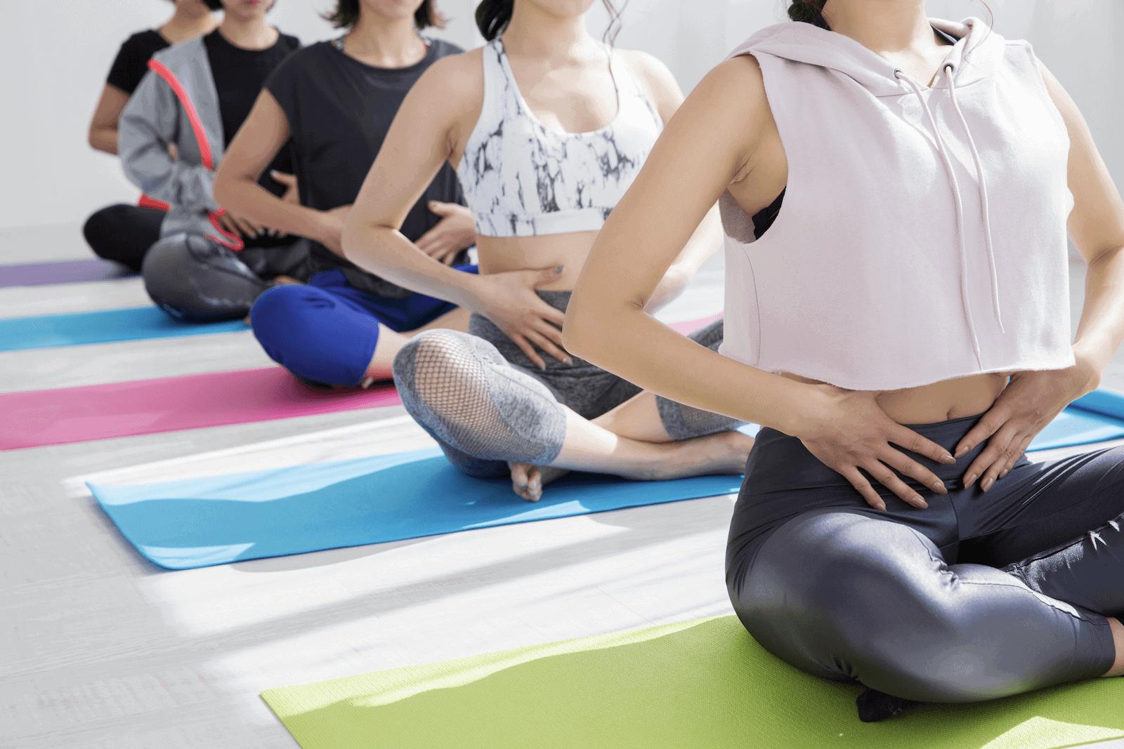 colonic: women sitting on yoga mats
