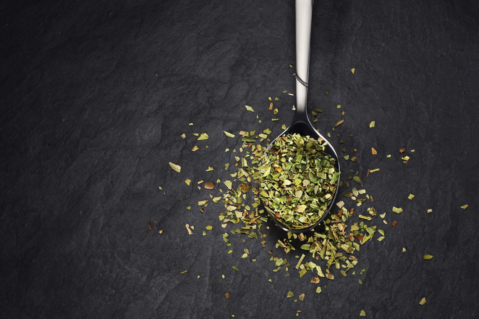 oil of oregano benefits: teaspoon with oregano spice